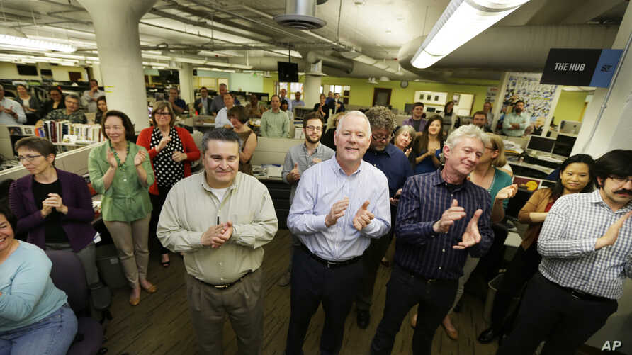 Seattle Times staffers applaud a speech in the paper's newsroom, April 20, 2015, after it was announced that the newspaper's staff had won the Pulitzer Prize for breaking news reporting for its coverage of the mudslide in Oso, Washington, that killed