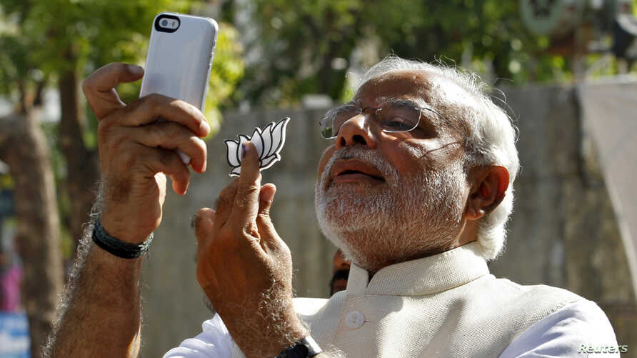 """FILE - Hindu nationalist Narendra Modi, the prime ministerial candidate for India's main opposition Bharatiya Janata Party (BJP), takes a """"selfie"""" with a mobile phone after casting his vote at a polling station during the seventh phase of India's gen"""