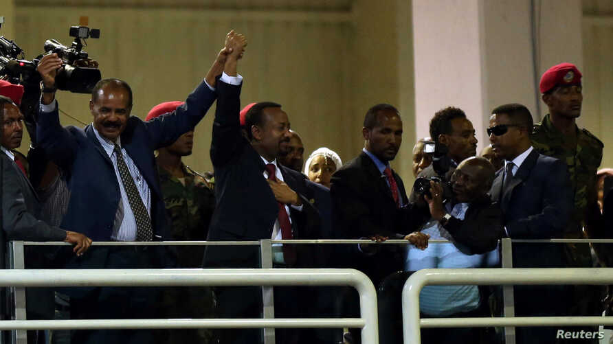 Eritrea's President Isaias Afwerki and Ethiopian Prime Minister Abiy Ahmed look at supporters as they attend a concert at the Millennium Hall in Addis Ababa, Ethiopia, July 15, 2018.