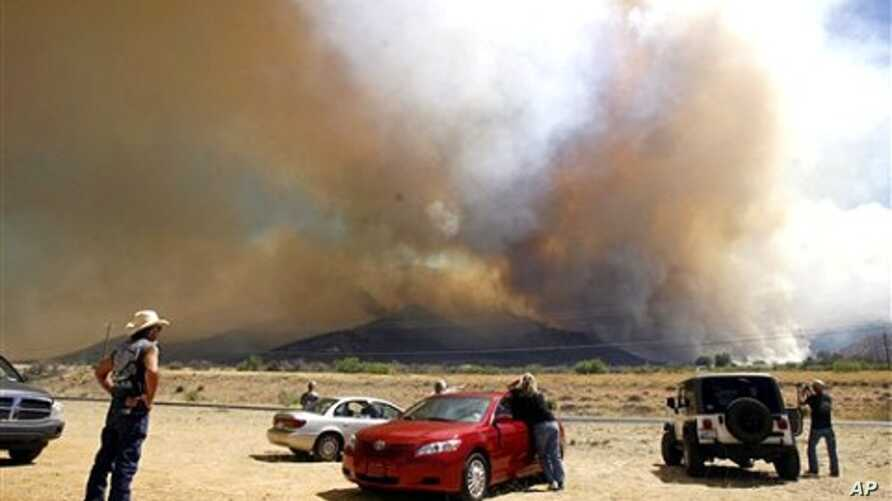 People watch the growing plume of smoke from across Highway 92 as the Monument Fire burns in the Huachuca Mountains near Sierra Vista, Arizona, June 14, 2011