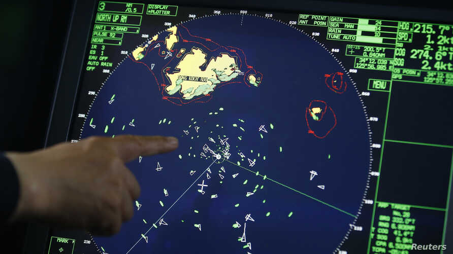 FILE - An official on South Korean Coast Guard ship points to a radar, April 17, 2014. Large South Korean ore carrier Stellar Daisy with 24 people onboard has gone missing in the South Atlantic.