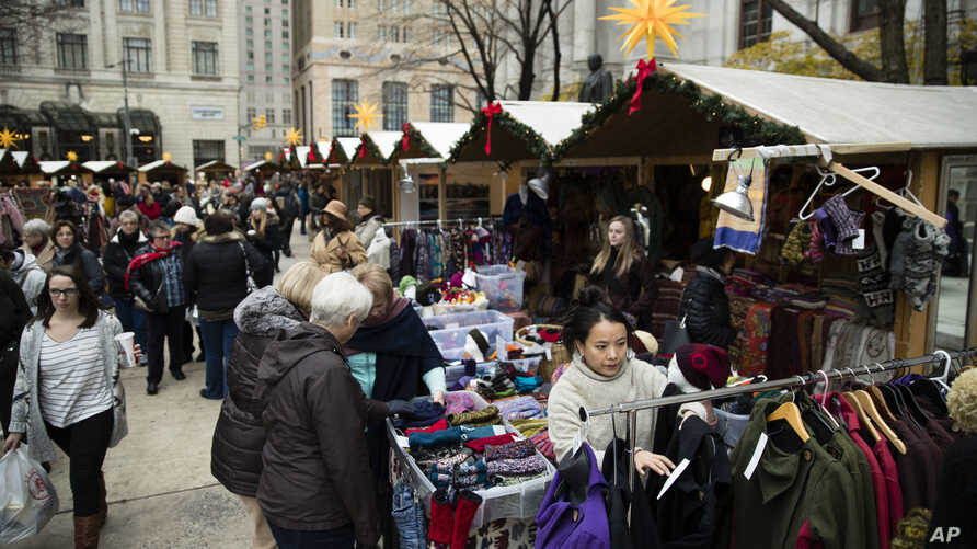Shoppers look for gifts in booths set up for the holidays around City Hall in Philadelphia, Dec. 8, 2016. New numbers from a key data source show that shoppers are so far spending at a decent, but slightly slower pace this holiday season compared to