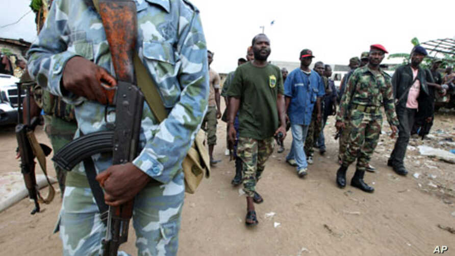 """A man known as Commander Bauer, the chief of a group of fighters which calls itself the """"invisible commandos"""", walks with his men in northern Abidjan's Abobo district. Fighting in Ivory Coast's main city is spreading and the death toll from a power s"""