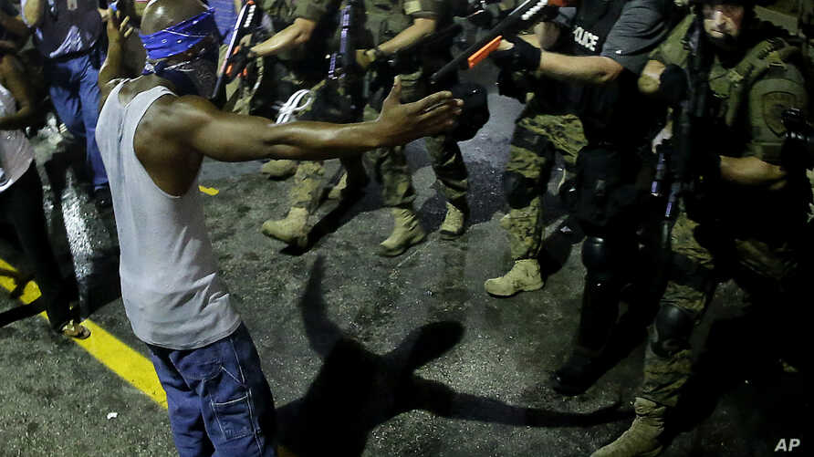 Police arrest a man as they disperse a protest in Ferguson, Mo., Aug. 20, 2014.