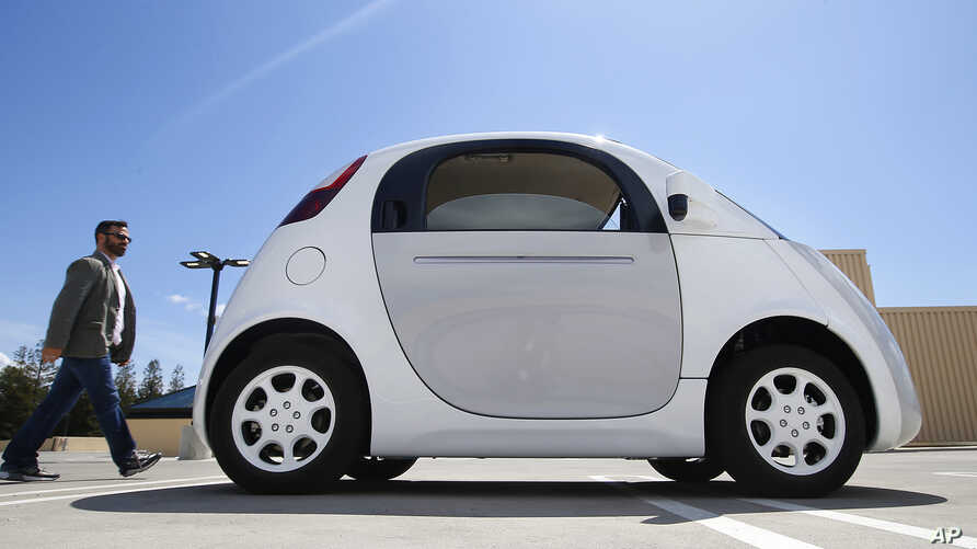 In this May 13, 2015 photo, a reporter walks toward Google's new self-driving prototype car during a demonstration at the Google campus in Mountain View, Calif.