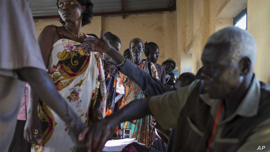 Voters wait in line to cast their vote, as others have their fingers dipped in ink to show they have done so, in an abandoned school used as a polling center in the disputed border region of Abyei, Oct. 27, 2013.