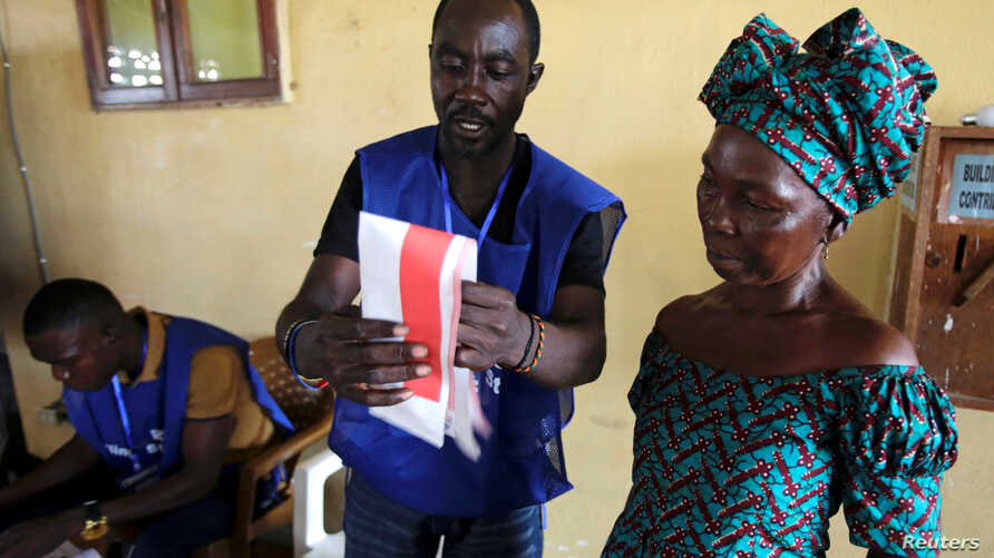 An election official shows to a woman how to cast her ballot during Liberia's presidential election in Monrovia, Liberia, October 10, 2017.