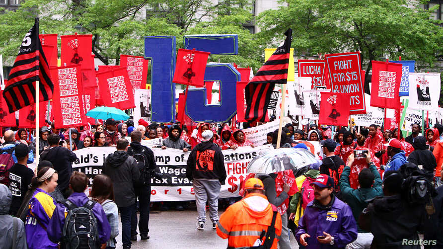 "FILE - Cooks, cashiers and other minimum wage earners join anti-Trump activists on a march for an increase in the minimum wage during a ""March on McDonald's"" in Chicago, Illinois, May 23, 2017."