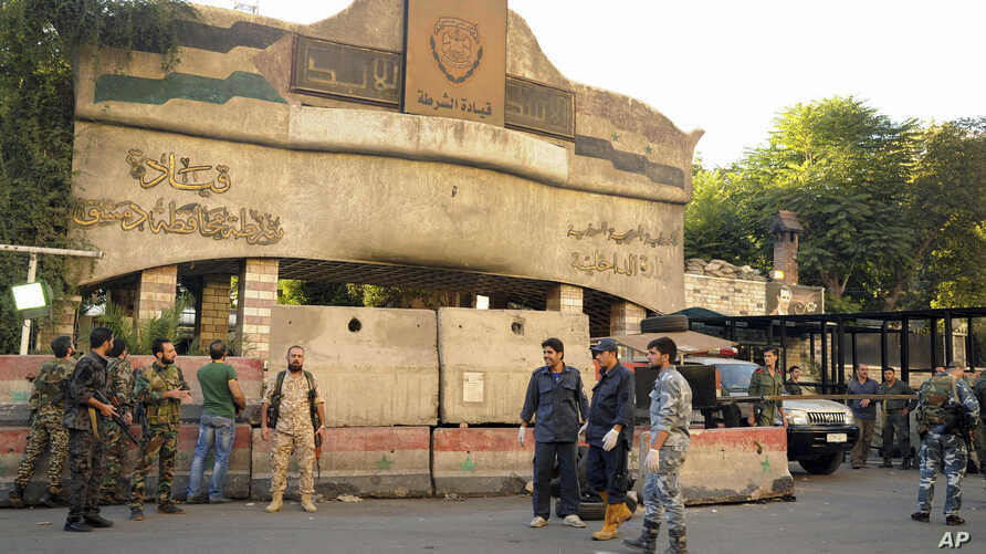 In this photo released by the Syrian official news agency SANA, Syrian soldiers and security officials gather at the scene of suicide bombings, outside police headquarters in central Damascus, Syria, Oct. 11, 2017.