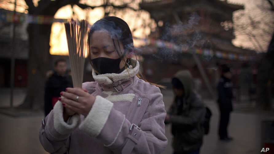 A woman holds sticks of incense as she prays at the Lama Temple in Beijing, Tuesday, Feb. 5, 2019. Chinese people are celebrating the first day of the Lunar New Year on Tuesday, the Year of the Pig on the Chinese zodiac.