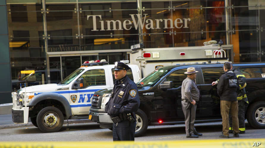 An officer keeps watch in front of the Time Warner Building, where NYPD personnel removed an explosive device Wednesday, Oct. 24, 2018, in New York.