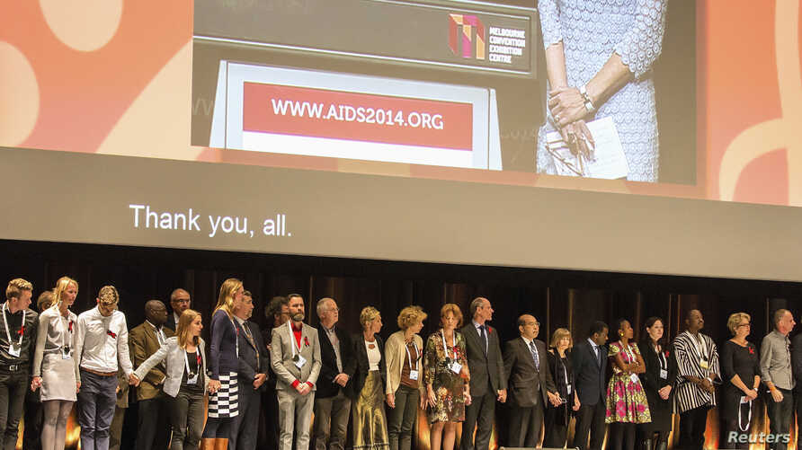 Delegates observe a minute's silence during the opening session, as a tribute to colleagues killed in the Malaysia Airlines flight MH17, at the 20th International AIDS Conference in Melbourne, July 20, 2014.