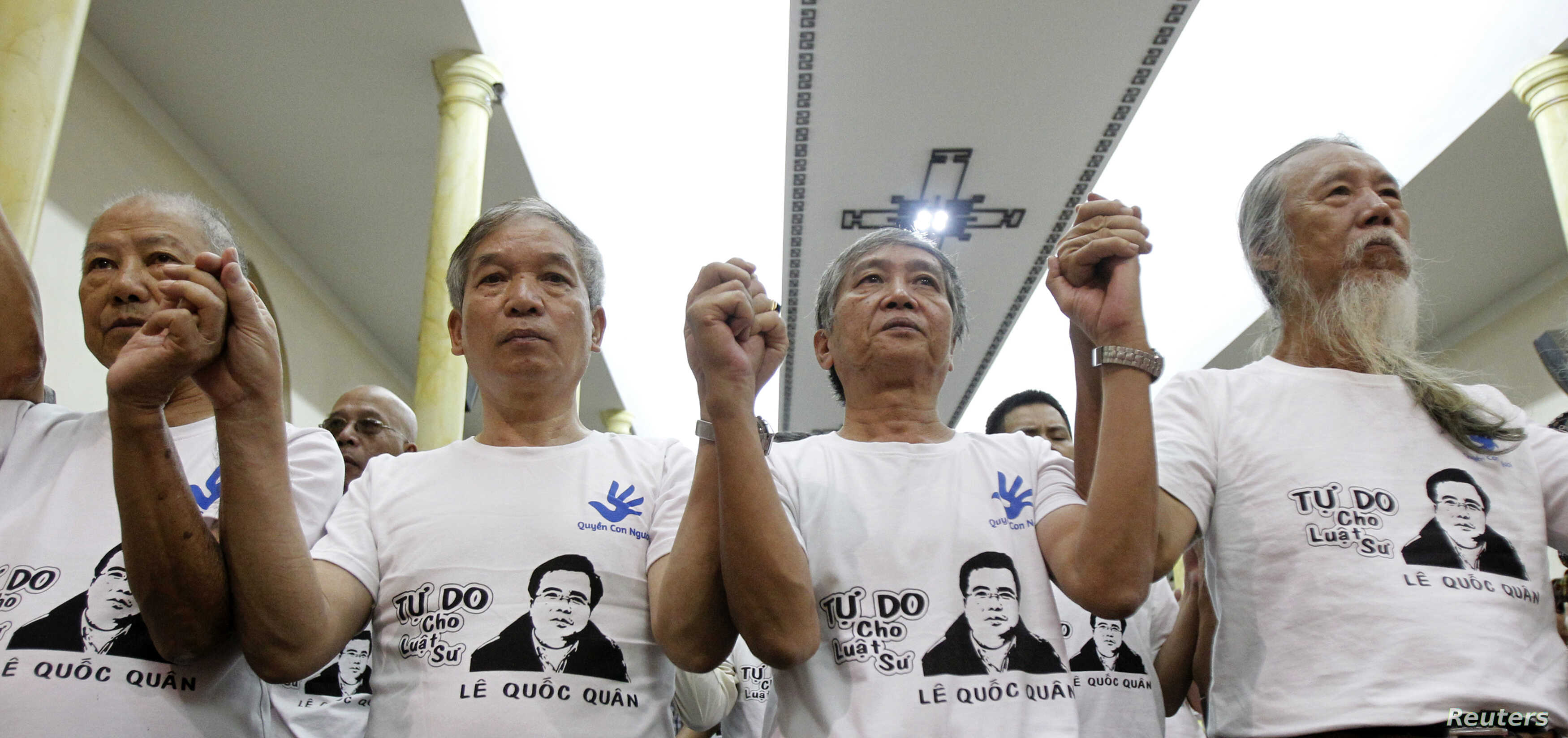 Friends and supporters wearing t-shirts with the image of lawyer Le Quoc Quan hold hands while attending a mass calling for Quan to be freed at Thai Ha church in Hanoi September 29, 2013. Participants during the mass prayer also called for justice fo