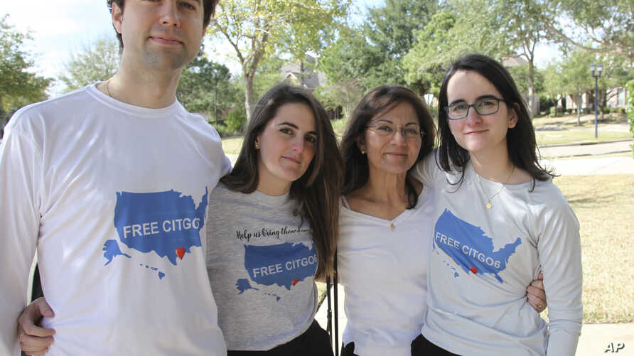 """Wearing T-shirts with the message """"Free the Citgo 6,"""" the Vadell family poses for a photo in Katy, Texas, Feb. 15, 2019."""