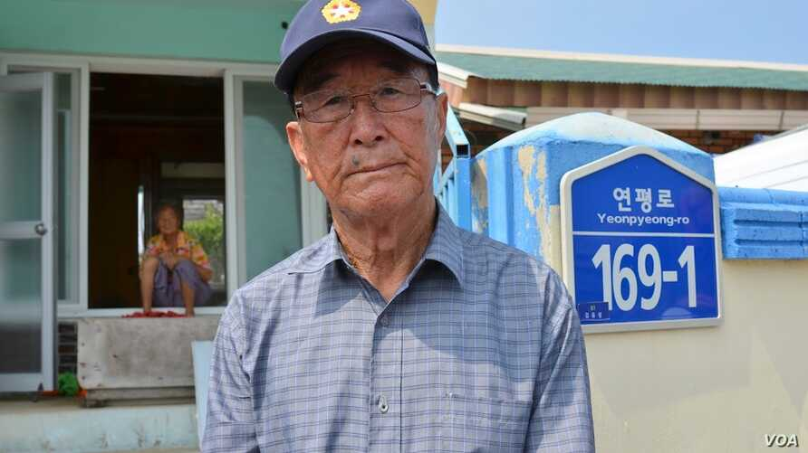 Kim Yoo-sung, 84, at the gate of his home that was severely damaged by the North Korean artillery attack. (Photo: VOA / Steve Herman)