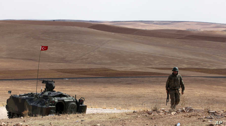 A Turkish soldier stands next to an armored vehicle stationed on a hill top overlooking the fighting positions between Syrian Kurds and Islamic State militants, about 10 kilometers in the west of Kobani in Syria, near Suruc, Turkey, Oct. 2, 2014.