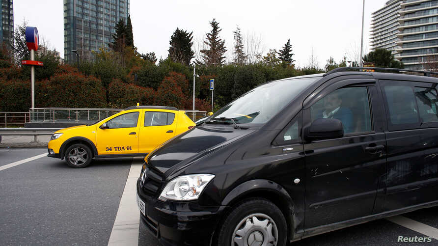 FILE - An Uber driver drives his car with a taxi seen in the background, in Istanbul, Turkey, March 15, 2018.