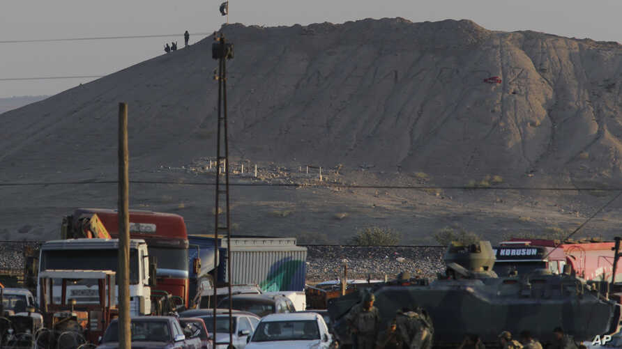 In this image shot from the outskirts of Suruc at the Turkey-Syria border, Turkish forces patrol the border as militants with the Islamic State group are seen after placing their group's flag on a hilltop at the eastern side of the town of Kobani, Sy