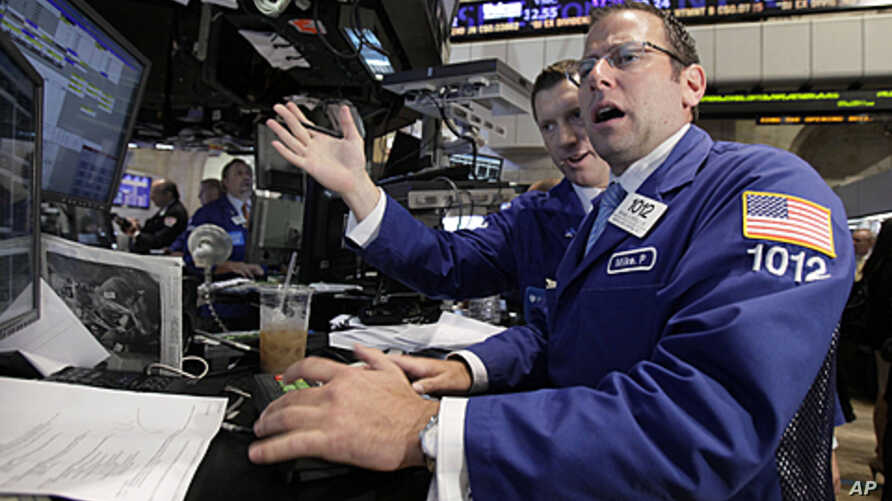 Michael Pistillo (R) works with a fellow specialist on the floor of the New York Stock Exchange, August 9, 2011