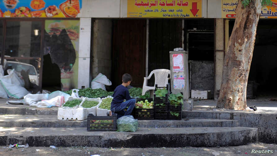FILE - A boy sells vegetables and fruits along a street in the Damascus suburb of Qudsaya, Syria, July 24, 2017.