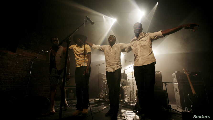 Malian band Songhoy Blues members, Nathanael Dembele (L-R), Garba Toure, Aliou Toure and Oumar Toure, react at the end of their concert at Village Underground in London, Britain, May 28, 2015.