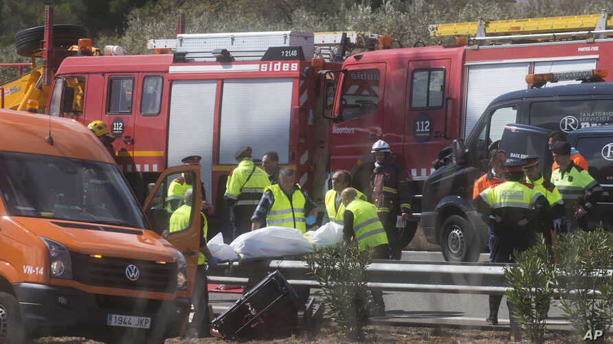 Undertaker workers carry the body of a person killed during a bus accident on the AP7 highway that links Spain with France along the Mediterranean coast near Freginals halfway between Valencia and Barcelona, Sunday, March 20, 2016.