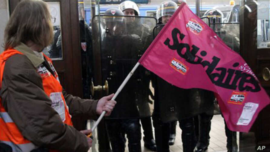 A demonstrator holds a trade union flag as French riot police officers secure the area at the Bordeaux train station, southwest France, Friday Oct. 22, 2010, during a demonstration against President Nicolas Sarkozy's bid to raise the retirement age t
