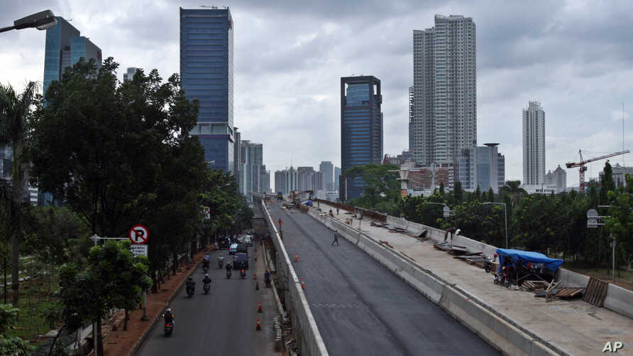 FILE - In this Jan. 11, 2013 photo, workers build an elevated highway in Jakarta, Indonesia.