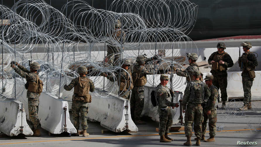 U.S. Marines help to build a concertina wire barricade at the U.S. Mexico border in preparation for the arrival of a caravan of migrants at the San Ysidro border crossing in San Diego, California, Nov. 13, 2018.