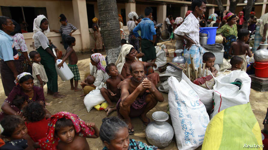 FILE - People from a Rohingya internally displaced persons (IDP) camp wait for a vehicle to return to their camp after waiting out cyclone Mahasen in a mosque outside Sittwe.