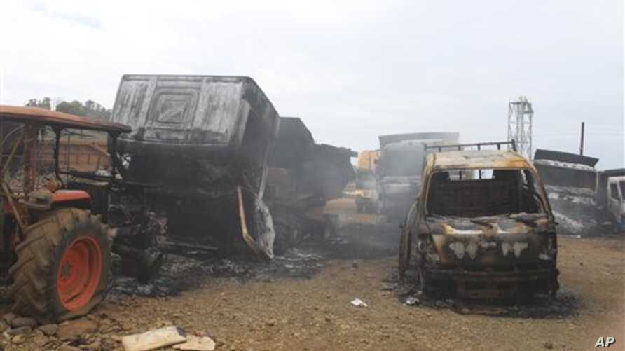 Trucks allegedly burned by communist rebels seen at the compound of Taganito Mining Corp, partly owned by a Japanese company, in Surigao del Norte province, southern Philippines on Tuesday Oct. 4, 2011.