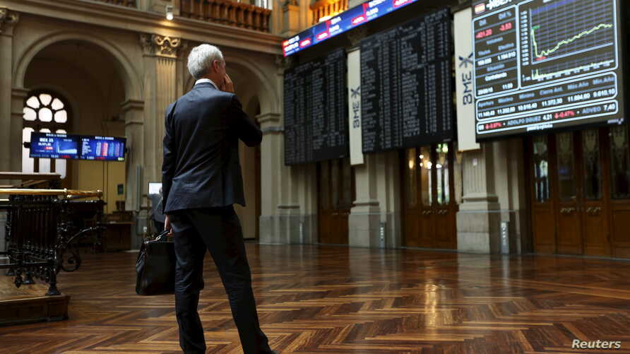 A trader looks at computer screens at Madrid's bourse, Spain, June 29, 2015.