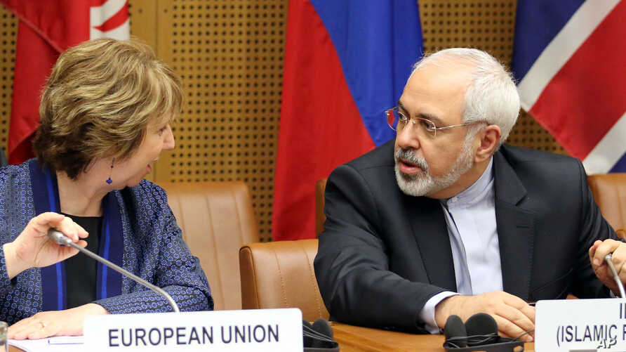 European foreign policy chief Catherine Ashton, left, and Iranian Foreign Minister Mohammad Javad Zarif, right, wait for the start of closed-door nuclear talks in Vienna, Austria, Tuesday, June 17, 2014
