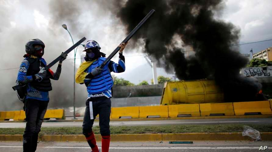 Demonstrators stand near a burning truck used as a barricade during a protest on the Francisco Fajardo highway outside La Carlota Air Base in Caracas, Venezuela, June 23, 2017.