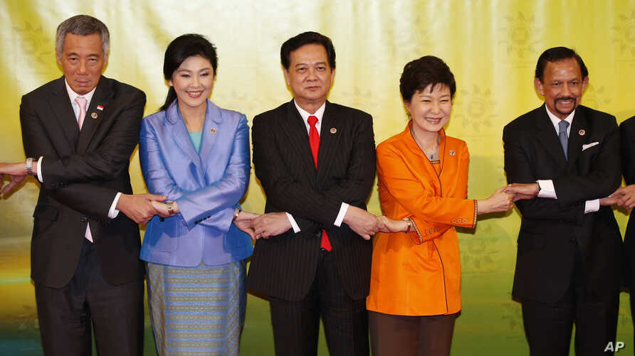 South Korean President Park Geun-hye, second right, joins hands with leaders of the Association of Southeast Asian Nations during a group photo session before the 16th ASEAN - Korea Summit in Bandar Seri Begawan, Brunei, Wednesday, Oct. 9, 2013. From