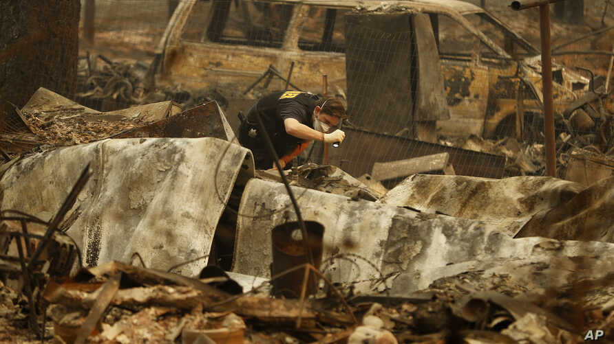A member of the Sacramento County Coroner's office looks for human remains in the rubble of a house burned at the Camp Fire  in Paradise, Calif., Nov. 12, 2018.