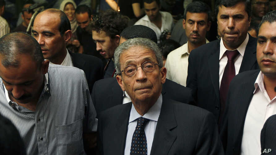 Egyptian presidential candidate Amr Moussa, center, attends a news conference in Cairo, May 16, 2012.
