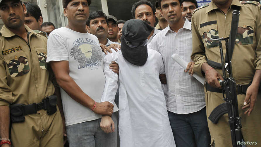 FILE - With his face covered, one of the alleged plotters in the 2008 Mumbai terror attacks is seen in Indian police custody.