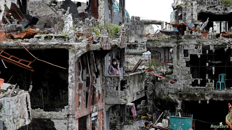 FILE - A woman stands at her ruined house, after residents were allowed to return to their homes for the first time since the battle between government troops and Islamic State militants began on May 2017, on Marawi, Philippines, April 19, 2018., 201
