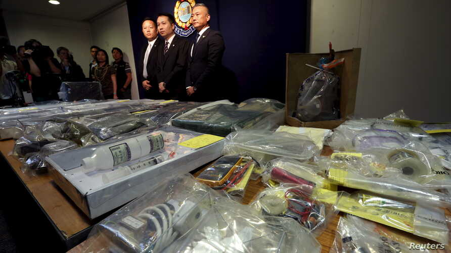 Officers from Police Organized Crime and Triad Bureau (L-R) Chief Inspector Tsue Chun-tung, Chief Superintendent Au Chin-chau and Superintendent Ng Wai-hon, pose in front of items relating to making explosives seized, during a news conference at poli