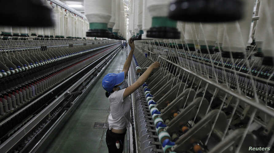A woman works at a yarn-weaving plant of the Ha Nam textile company in Phu Ly city, about 60 km (37 miles) south of Hanoi, July 4, 2013.