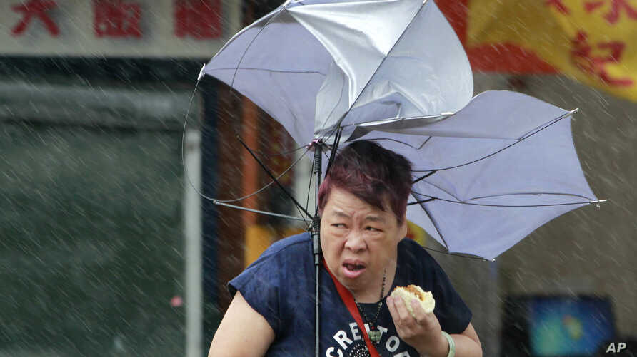 Taiwan Typhoon: A woman eats and struggles with her umbrella against powerful gusts of wind generated by typhoon Megi across the the island in Taipei, Taiwan, Tuesday, Sept. 27, 2016.