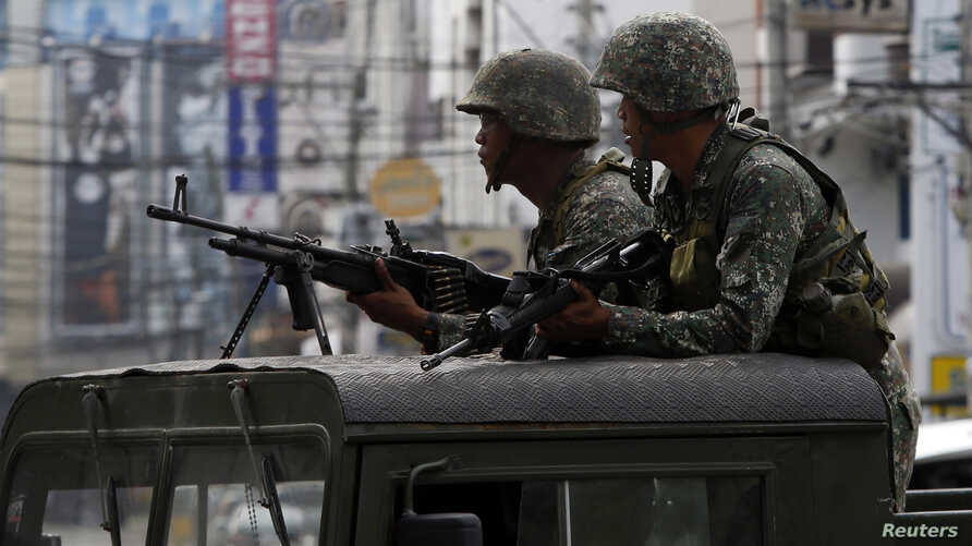 Members of the Philippine Marines hold their weapons aboard a truck as they block a road during fighting between government soldiers and Muslim rebels of Moro National Liberation Front (MNLF) in Zamboanga city in southern Philippines September 15, 20
