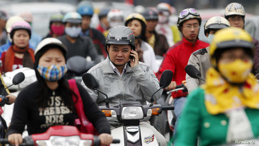 FILE - A motorist talks on his mobile phone while waiting at a traffic junction in Hanoi, Oct, 31, 2011.