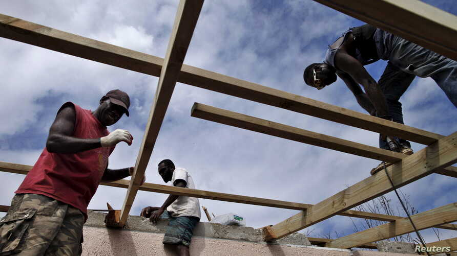 Workers repair the roof of a holiday resort days after Cyclone Pam in Port Vila, capital city of the Pacific island nation of Vanuatu March 19, 2015. REUTERS/Edgar Su   - RTR4TYRI