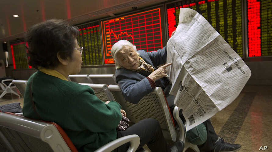 Chinese stock investors look over a newspaper in a brokerage house in Beijing, Jan. 27, 2016. Chinese stocks sank again Wednesday but other Asian markets rose following Wall Street's gain.