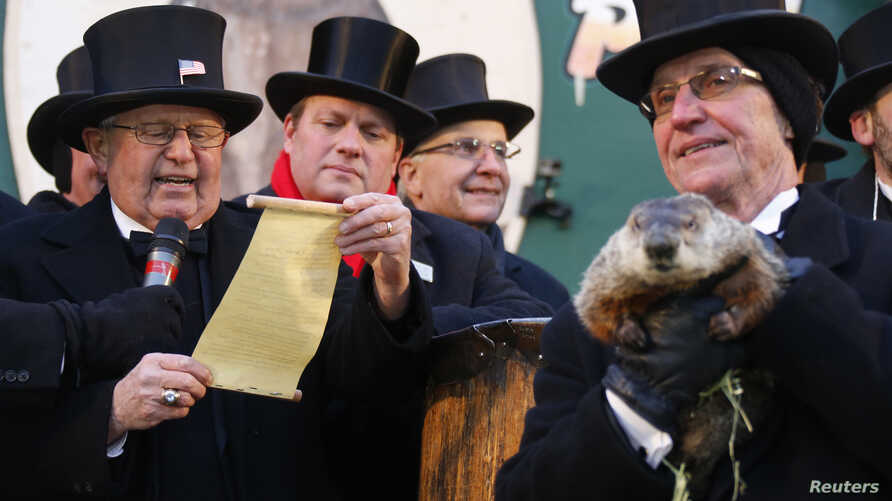 Groundhog co-handler Ron Ploucha (R) holds Punxsutawney Phil as the Groundhog Club's Bob Roberts (L) reads the famous groundhog's annual weather prediction on Gobbler's Knob in Punxsutawney, Pennsylvania, on the 127th Groundhog Day, February 2, 2013