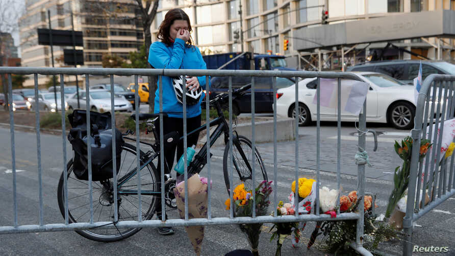 Kate Anstett, 22, wipes tears from her eyes by a makeshift memorial for victims of Tuesday's attack outside a police barricade on the bike path next to West Street in New York City, Nov. 1, 2017.