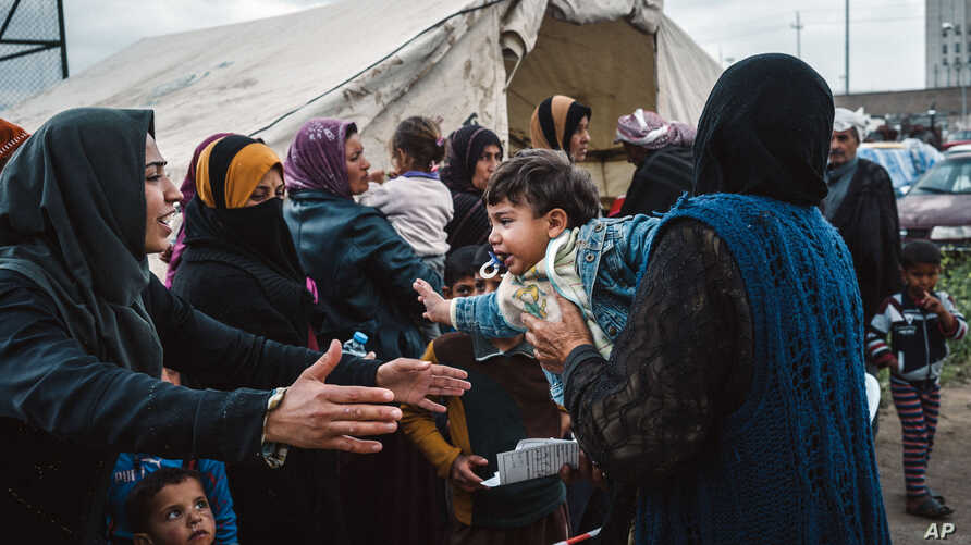 Civilians displaced by heavy fighting between Iraqi security forces and ISIS militants line up outside a tent set up by MSF, or Doctors Without Borders, to provide medical aid, in Makhmour, east of Mosul, Iraq, March 28, 2016.