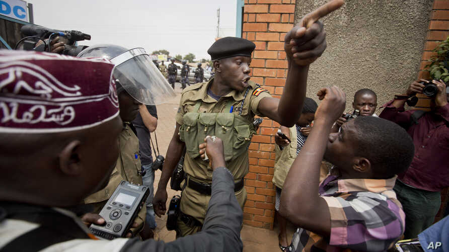 A policeman argues with a supporter of opposition leader Kizza Besigye at the gates of his party headquarters, before police who had surrounded it raided the building, in Kampala, Uganda, Feb. 19, 2016.